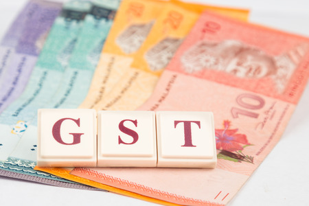 Concept - GST word against Malaysian Ringgit notes as  backdrop Stock Photo