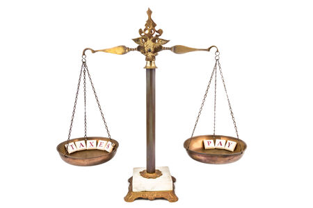 equal to: Balanced Scale between INCOME and TAXES Stock Photo