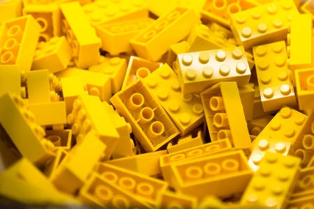 yellow block: Pile of Building Blocks with focus and highlight on a selected piece with available light Stock Photo