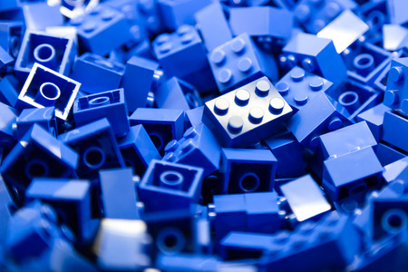 Pile of Building Blocks with focus and highlight on a selected piece with available light Stock Photo