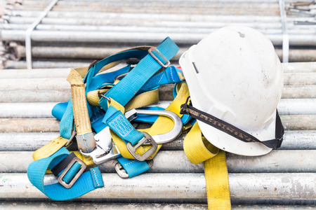 Safety helmet and safety harness at a construction site Stockfoto