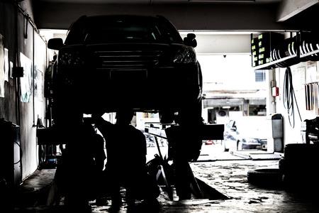 mecanico: Mec�nica inspeccionar los coches en un peque�o taller en la silueta.