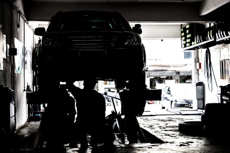 Mechanics inspecting cars in a small workshop in silhouette.