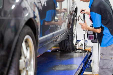 automobiles: A mechanic fixing a wheel alignment devise onto the wheel of a vehicle.