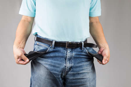 penniless: Men in jeans pulling his empty pockets Stock Photo