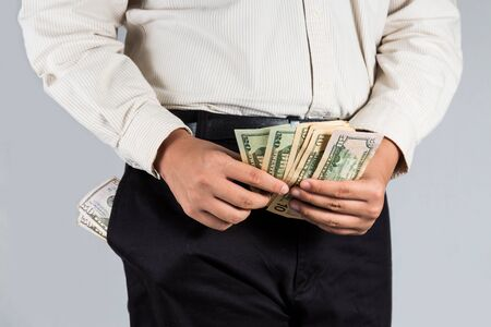 abundant: Man with abundant of money in his pockets, counting some note Stock Photo