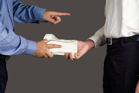 another: Man point and hand an envelope full of money to another person.