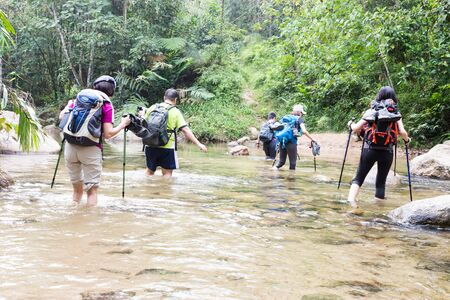 Group of people crossing river while hiking in a tropical forest photo
