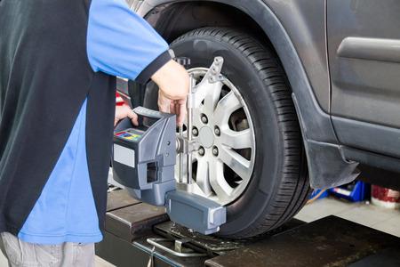 alineaci�n: Mec�nico que fija el dispositivo de alineaci�n de las ruedas en una rueda de coche. El foco est� en la rueda del coche y alineaci�n de las ruedas dispositivo.