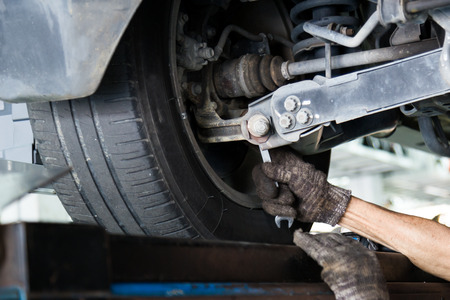 Mechanic adjusting the nut on the chamber during wheel alignment process