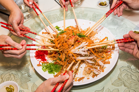 A group of people mixing and tossing Yee Sang dish with chop sticks. Yee Sang is a popular delicacy taken during Chinese New Year, believed to bring good fortune and luck Stock Photo