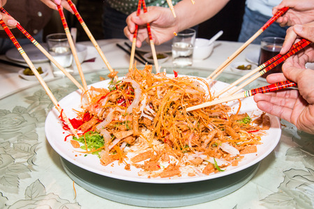 A group of people mixing and tossing Yee Sang dish with chop sticks. Yee Sang is a popular delicacy taken during Chinese New Year, believed to bring good fortune and luck photo