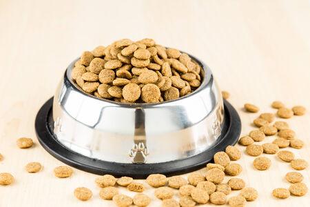 hueso de perro: Kibbles de perro en un tazón en suelo de madera