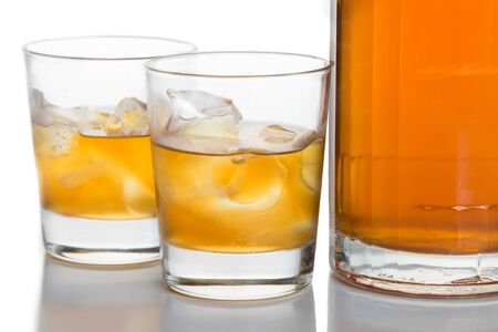 whiskey on the rocks: Close up on two glasses of whiskey on the rocks, with a whiskey bottle  in white background