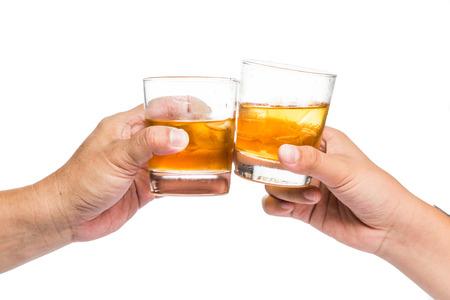 2 つの白い背景の岩に乾杯ウイスキーを手します。