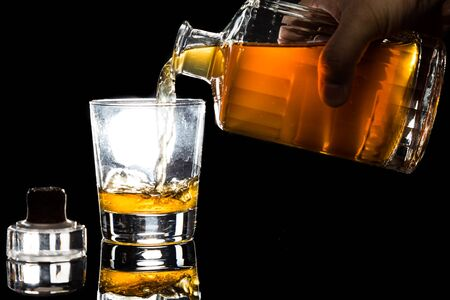 Hand pouring a glass of whiskey from a bottle in dark background photo