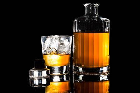 whiskey on the rocks: Whiskey on the rocks, with a whiskey bottle in dark background