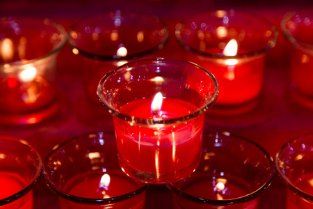 easter candle is burning: Red tea lights in glass jar illuminates a dark surrounding