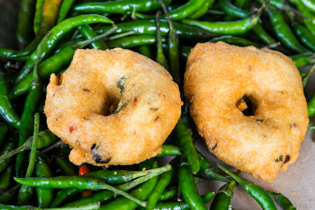 urad dal: Uluntu Vadai with green chili pepper, a popular Southern Indian deep fried snack Stock Photo