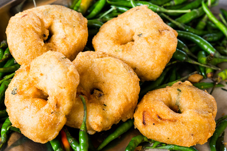 fried snack: Uluntu Vadai with green chili pepper, a popular Southern Indian deep fried snack Stock Photo