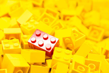 yellow lego block: Pile of yellow color building blocks with selective focus and highlight on one particular red block using available light.