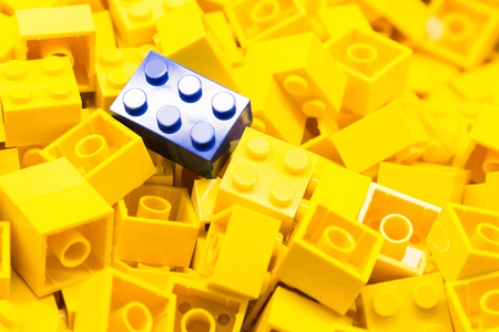 yellow lego block: Pile of yellow color building blocks with selective focus and highlight on one particular blue block using available light.