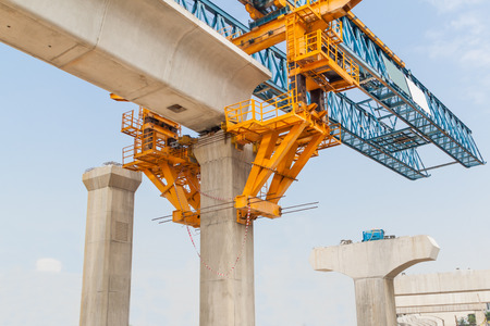 Construction of a mass transit train line in progress with heavy infrastructure. This photo shows the progress in joining the various blocks/modules of the line with heavy equipment.