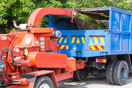 Wood chipper machine releasing the shredded leafs and trunks into a truck
