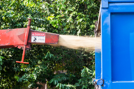 tree removal service: Wood chipper machine releasing the shredded leafs and trunks into a truck
