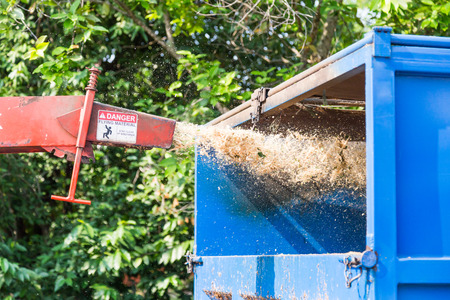 Wood chipper machine releasing the shredded leafs and trunks into a truck Stock Photo