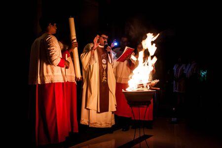 sacerdote: KUALA LUMPUR 19 de abril de 2014: los cat�licos celebran la misa de Pascua v�spera de media noche en la iglesia de Santo Tom�s Moro, Shah Alam en Malasia. Los servicios se llevan a cabo en otras iglesias cat�licas tambi�n. El sacerdote se ilumin� el fuego nuevo en el Cirio Pascual como pa
