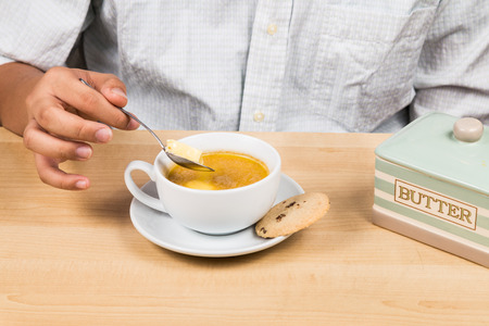 bullet proof: Person adding butter to coffee Stock Photo