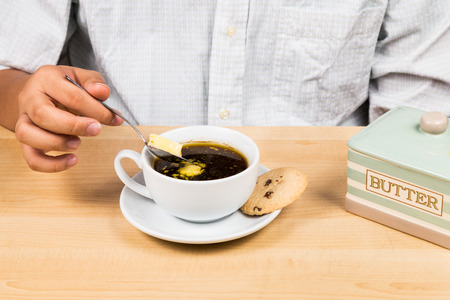 bullet proof: Person adding butter to black coffee Stock Photo
