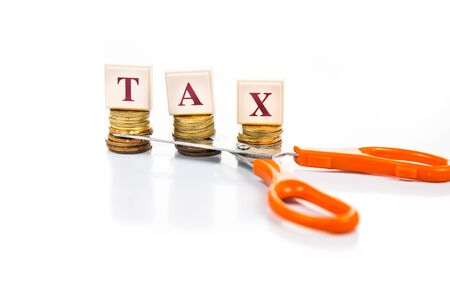 savings problems: Cut taxes concept with coins and scissors
