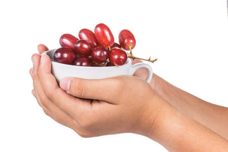 Hands holding a cup full of red grapes photo