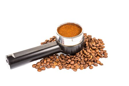 grounded: Coffee portafilter filled with finely grounded coffee, and with coffee beans scattered around Stock Photo