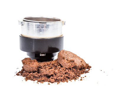coffee grounds: Spent or used coffee grounds with portafilter at the background