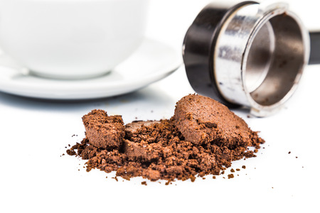 spent: Spent or used coffee grounds with portafilter and a cup of freshly brewed coffee in the background