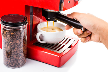 Hand operating red color coffee machine brewing espresso photo