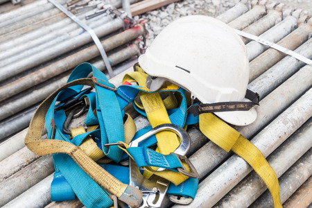 health dangers: Safety helmet and harness at construction site