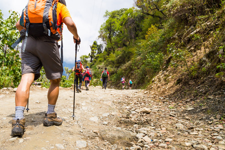 nepal: A group of people trekking on dirt road in Nepal