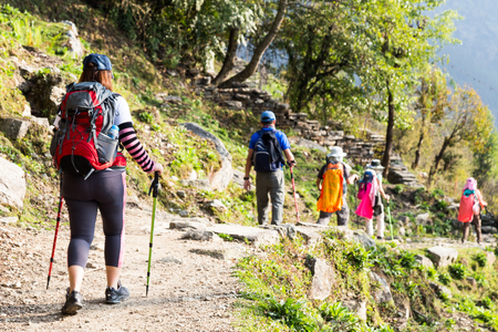 Female trekking through a scenic trail along with other people Banco de Imagens