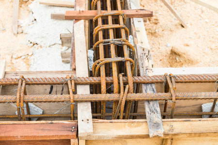 cement pole: Close up of wooden mold with steel rod forming the foundation beam at construction site