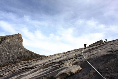lows: Mount Kinabalu summit with hikers in silhouette