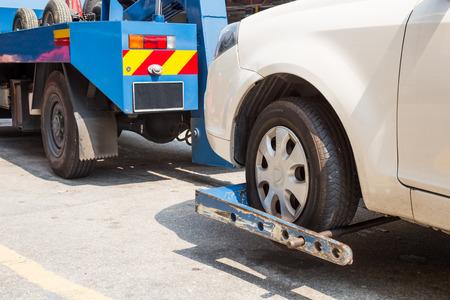 pickup truck: Gr�a remolca un coche averiado en la calle Foto de archivo
