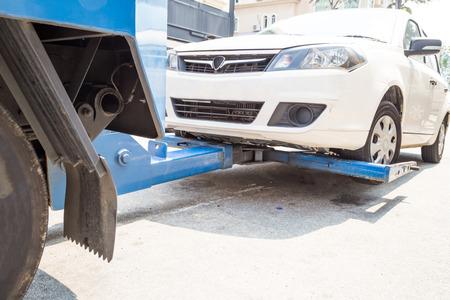 camioneta pick up: Gr�a remolca un coche averiado en la calle Foto de archivo