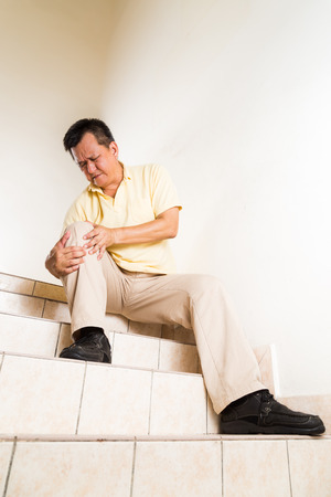 senior pain: Matured man suffering acute knee joint pain seated on staircase Stock Photo