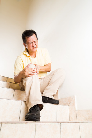 Matured man suffering acute knee joint pain seated on staircase Stockfoto