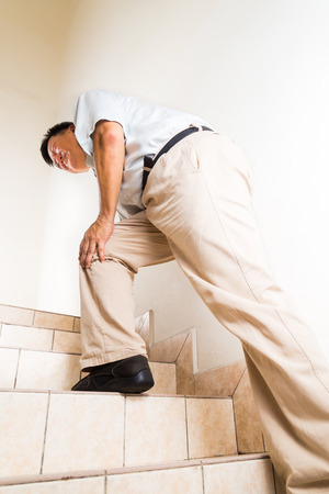 acute: Matured man suffering acute knee joint pain climbing steps Stock Photo