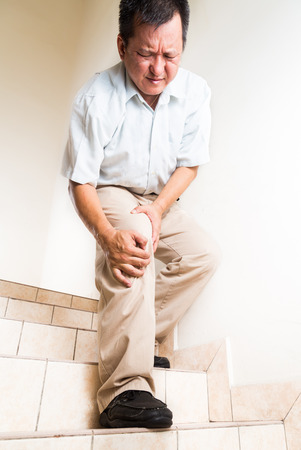 Matured man suffering acute knee joint pain descending steps
